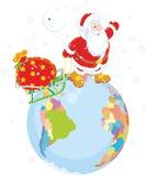 Jultomten med gåvor på ett jordklot Arkivbilder