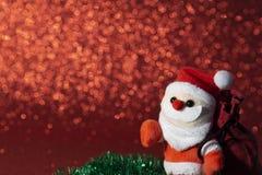 Jultomten med julgåvapåsen på röd bakgrund arkivbilder