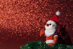 Jultomten med julgåvapåsen på röd bakgrund arkivbild