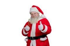 Jultomten med röret som ger upp tummen Arkivbild