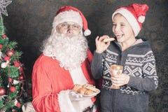 Jultomten och den roliga pojken med kakor och mjölkar på jul Arkivfoto