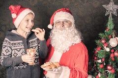 Jultomten och den roliga pojken med kakor och mjölkar på jul Arkivfoton