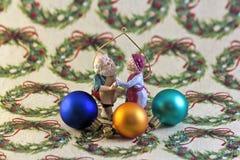 Jultomten och fru Claus med prydnader på inpackningspapper arkivbilder