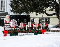 Jultomten och slädegräsmattagarnering Arkivfoto