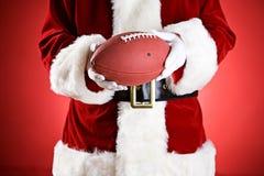 Jultomten: Rymma en amerikansk fotboll Arkivfoto