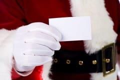 Jultomten: Santa Claus Holding Out Business Card Fotografering för Bildbyråer
