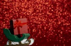Jultomten släde och gåvaask på gullig röd prickbakgrund arkivfoto