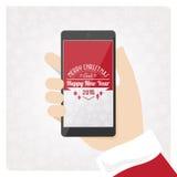 Jultomten smartphone Arkivfoto