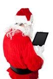 Jultomten som är upptagen i fungerande minnestavlaPC Arkivbild