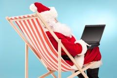 Jultomten som arbetar på bärbara datorn som placeras i en soldagdrivare Royaltyfri Bild