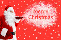 Jultomten som blåser glad jul i snö Arkivbild