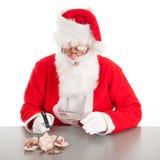 Jultomten som bryter den fattiga spargrisen Royaltyfri Fotografi
