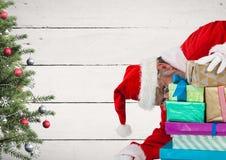 Jultomten som döljer bak gåvaaskar arkivbild