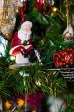 Jultomten som fiskar i en dekorativ prydnad för träd Arkivbild