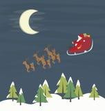 Jultomten som flyger över skogen Arkivbilder