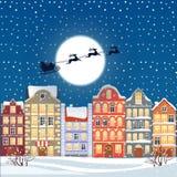Jultomten som flyger till och med natthimlen under den gamla stadillustrationen för jul Tecknad filmbyggnadsbakgrund triumfsikt f Royaltyfri Foto