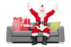 Jultomten som gör en gest lycka som placeras på soffan med gåvor Arkivfoto