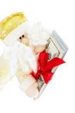 Jultomten som ger bunten av dollar Arkivfoto