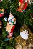 Jultomten som häller tesith en dekorativ prydnad för docka Arkivfoton
