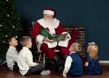 Jultomten som läser till ungar Arkivfoto