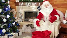 Jultomten som packar påsen med gåvor, julgåvor för lydiga barn, rum med spisen arkivfilmer