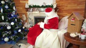 Jultomten som packar påsen med julgåvor, rum med spisen, Santa Claus post, träd x-mas lager videofilmer