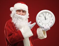 Jultomten som pekar på klockan som visar fem minuter till midnatt Arkivbilder
