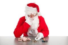 Jultomten som räknar mynt arkivbild