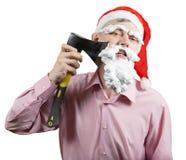 Jultomten som rakar hans skägg med en yxa Arkivfoto