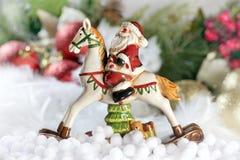 Jultomten som rider en häst Arkivfoto