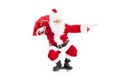 Jultomten som rider en skateboard Fotografering för Bildbyråer