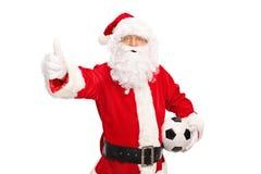 Jultomten som rymmer en fotboll och ger upp tummen Arkivbilder