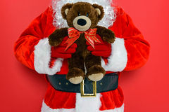 Jultomten som rymmer en nallebjörn royaltyfri foto