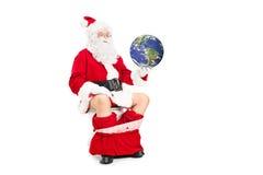 Jultomten som rymmer planeten i handen som placeras på toalett Arkivbild