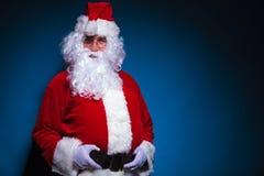 Jultomten som ser kameran, medan rymma hans bälte Arkivbilder
