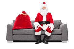 Jultomten som sitter på en soffa med påsen av gåvor Arkivbild