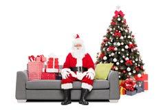 Jultomten som sitter på en soffa vid en julgran fotografering för bildbyråer