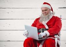 Jultomten som sitter på stol och använder bärbara datorn Royaltyfri Fotografi