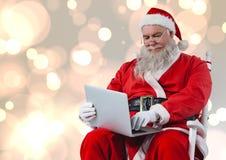 Jultomten som sitter på stol och använder bärbara datorn Royaltyfri Bild
