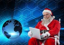 Jultomten som sitter på stol och använder bärbara datorn 3D Arkivbild