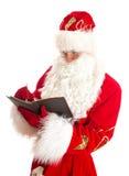 Jultomten som skriver listan av gåvor Arkivfoto