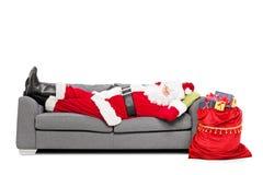 Jultomten som sover på soffan Arkivfoton