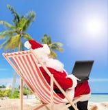 Jultomten som spelar med bärbara datorn på en strand Royaltyfri Bild