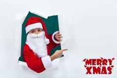 Jultomten som ut poppar från hålet och pekar för att kopiera utrymme Royaltyfri Fotografi