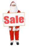 Jultomten som visar anslagstavlan med den Sale inskriften Royaltyfri Bild
