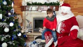Jultomten välkomnar pysen, unge får julgåva sitter på den Santa Claus varven, gåvor för barn lager videofilmer