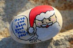 Jultomten vänder mot målat på ett litet vaggar har vara dig bra Arkivbild