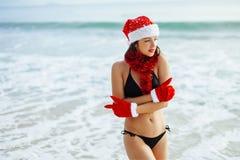 Jultomtenflicka i bikini på strandsemesterorten, i att få för santa hatt Fotografering för Bildbyråer