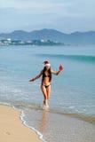 Jultomtenflicka i bikini på strandsemesterorten med gåva Arkivfoto