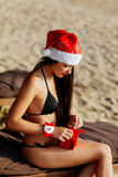 Jultomtenflicka i bikinin som packar upp julgåvan Royaltyfri Bild